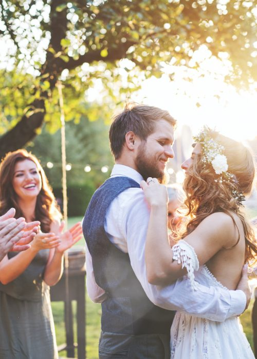 Bride and groom dancing at wedding reception outside in the backyard.